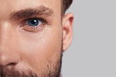 Close up of good looking young man half face looking at camera while standing against grey background
