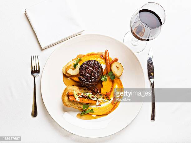 Looking down at delicious steak meal served with red wine