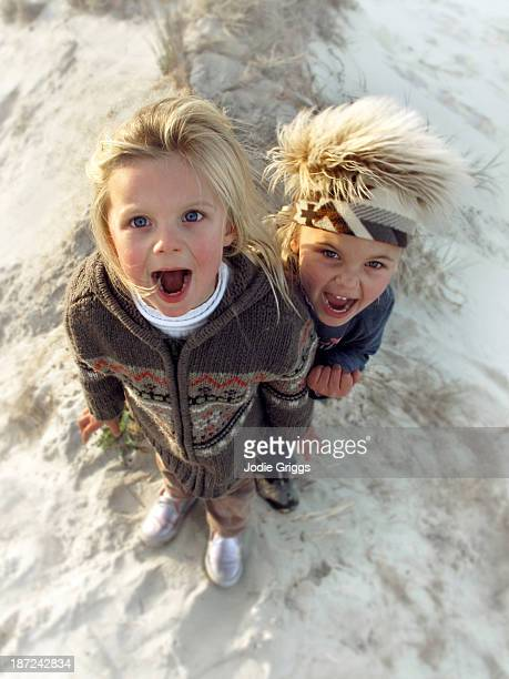 Looking down at two children yelling on sand dune