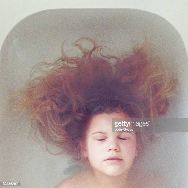 Looking down on child with long hair in bathtub