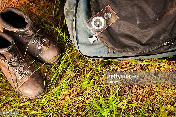 Looking down on hiking boots, backpack and compass, outdoors