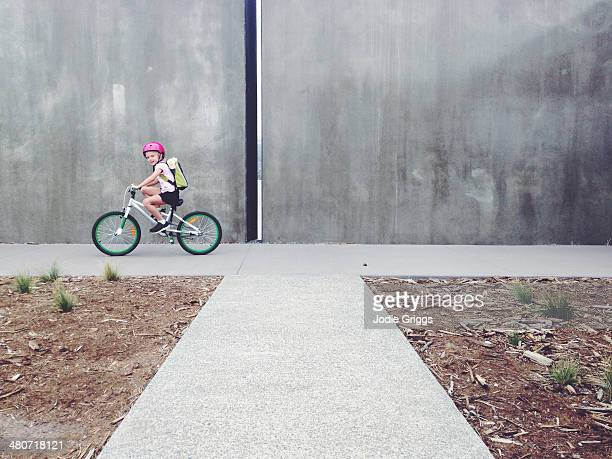 Looking down path at child riding a bicycle