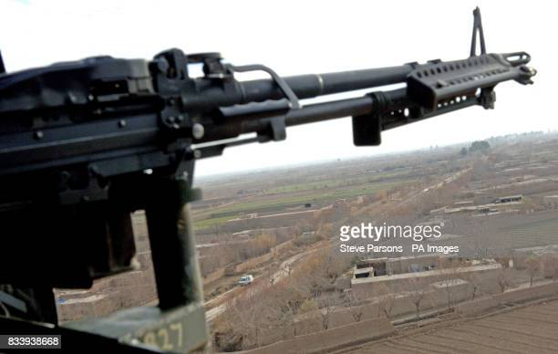 Looking down the barrel of a 50 calibre machine gun of an RAF Chinook Helicopter flying over the Afghanistan countryside