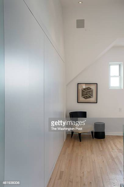 Looking down the long hall of seamless closet doors in to the bedroom of the condo of David Sayles in Washington DC December 18 2014