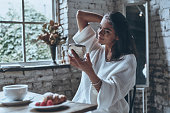 Attractive young woman looking in the mirror while having breakfast at home