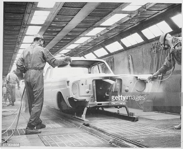 Looking like astronauts in their protective respirators and special uniforms sprayman at Ford Motor Company's Lorain Ohio Assembly Plant paint a 1964...