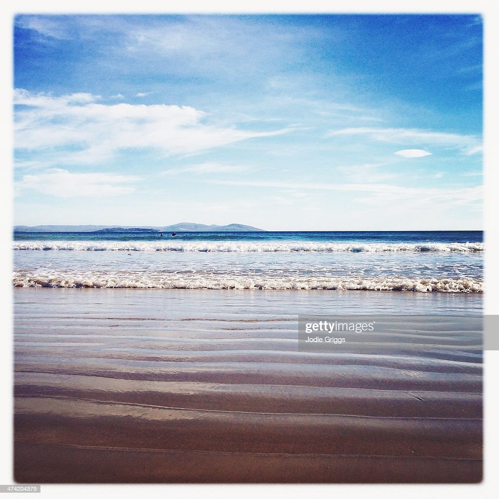 Looking out across rippled sand towards the ocean : Stock Photo