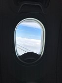 Looking out an airplane window with clouds and blue sky