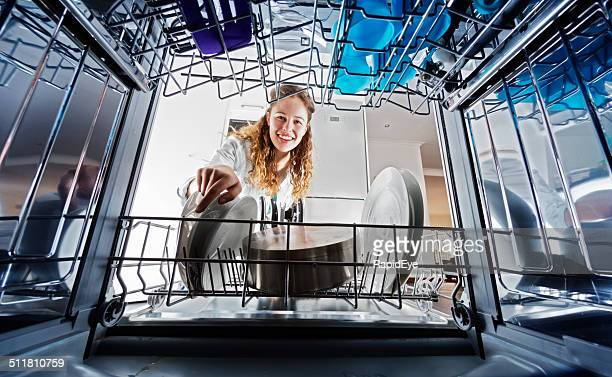 Looking out from dishwasher interior at young woman loading dishes