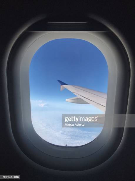 Looking out the airplane window at blue sky and clouds