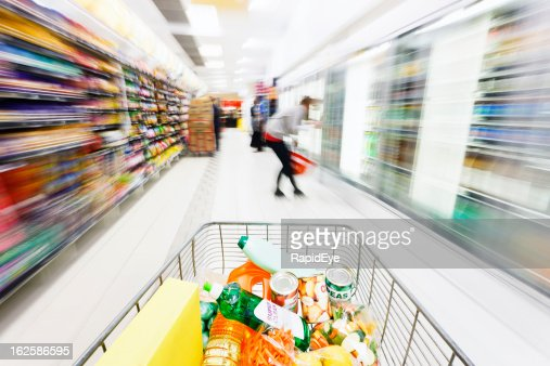 Looking over shopping cart at motion-blurred supermarket aisle