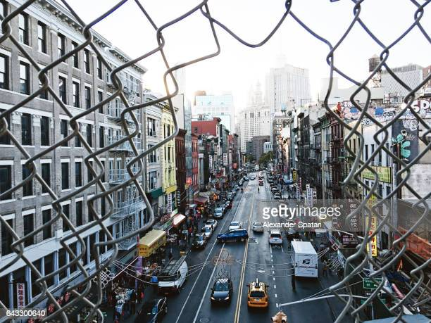 Looking through a chained fence at Manhattan skyline and Chinatown, New York, United States