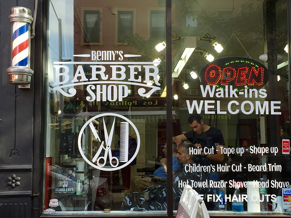 window of a barber shop that also has a barbers pole on the exterior ...