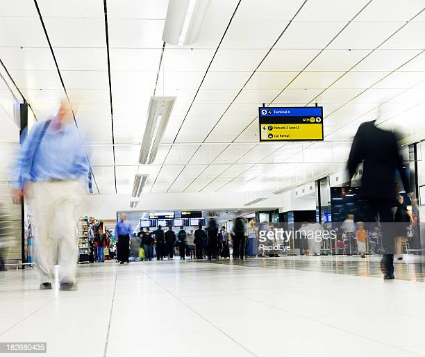 Looking through an airport concourse at people waiting in line
