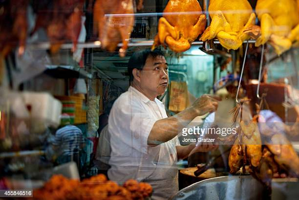 Looking through the glass window of a kitchen where there are ducks and chicken on a skewer whilst the chef behind is serving traditional Asian meals