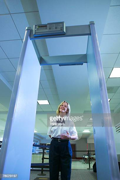 Looking through the metal detector to an airport security officer signaling a traveler to step forward