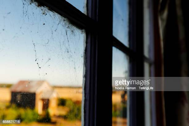 Looking through the window: (defocused) a small church in a farm and a spider web, Victoria. Australia
