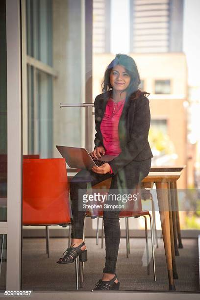 looking through window at young businesswoman