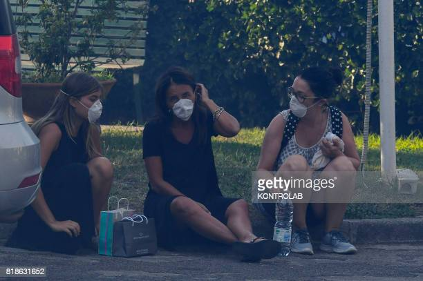 Looking tired and wearing masks some people rest by the side of the road during a vast fire that threatened inhabited areas between Naples and Campi...