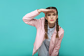 looking too far. portrait of beautiful cute girl standing with makeup and brown pigtail hairstyle in striped light blue shirt pink jacket. indoor, studio shot isolated on blue or green background.