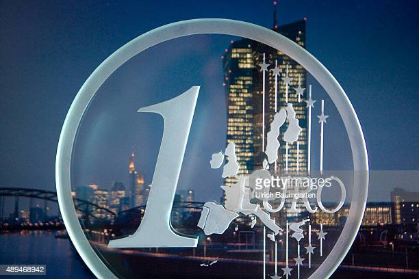 Looking trough a 1 Euro coin from glas In the background the building of the European Central Bank in Frankfurt