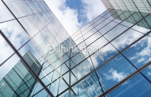 Looking up a reflections on glass covered corporate building : Stock Photo