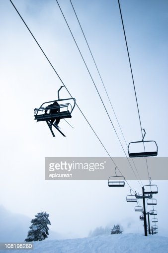 Looking Up at Skier Riding Ski Lift on Mountain