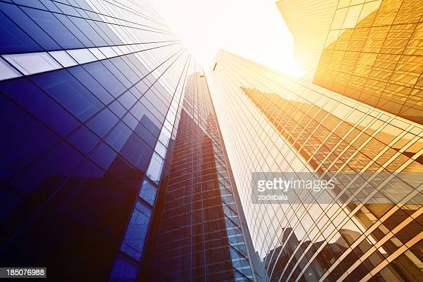 Looking up at tall buildings with sun shining down