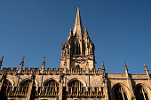 Looking up at the side and spire of the University Church of St Mary the Virgin as it overlooks High Street in the University City of Oxford