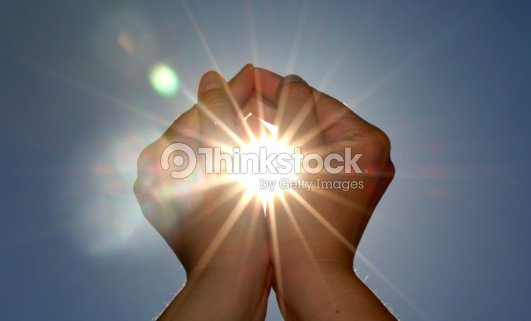 Looking up at two hands cupping the sun : Stock Photo
