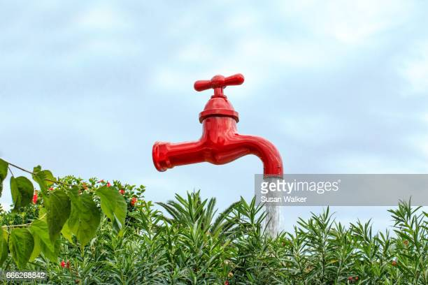 Looking up to a large red flowing tap outdoors
