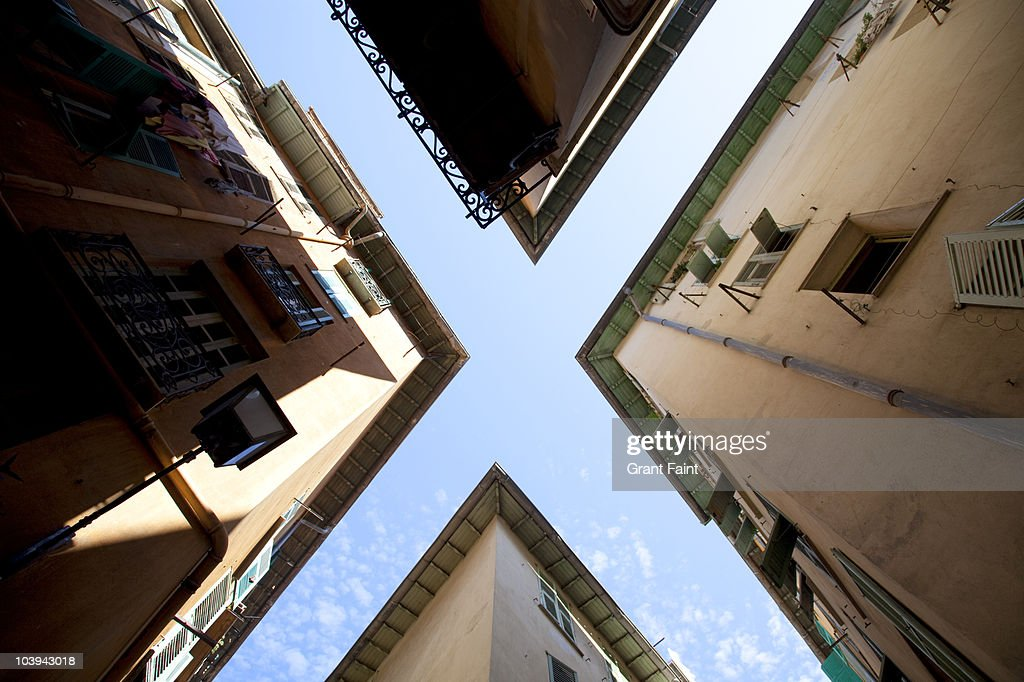 Looking up to sky through buildings.