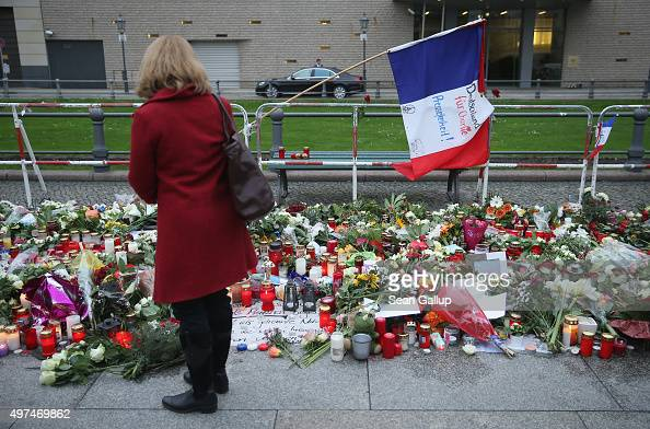 A looks at candles messages and flowers left by mourners outside the French Embassy commemorating the victims of last Friday's terrorist attacks in...