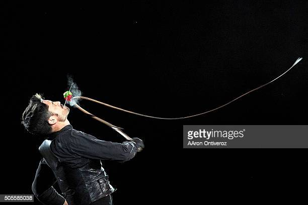 Loop Rollins snaps the stem of a rose in his mouth with a whip during the Martin Luther King Jr African American Heritage Rodeo of Champions on...