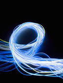 Looped bundle of fibre optic wires against black background, close-up