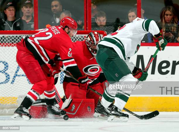 A loose puck rolls in front of Brett Pesce and Scott Darling of the Carolina Hurricanes duing an NHL game against the Minnesota Wild on October 7...