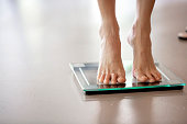 Legs of a woman standing on a weight scale, selective focus