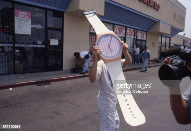 A looter holds a giant prop Swatch Watch on Vermont Ave after widespread riots that erupted after the acquittal of 4 LAPD officers in the videotaped...