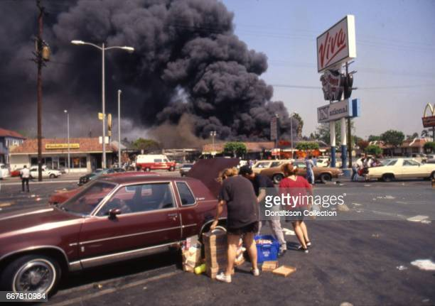 Looters at Viva Shopping center across with Pioneer Chicken across with a Winchell's Donut shop next to a billowing fire during widespread riots that...