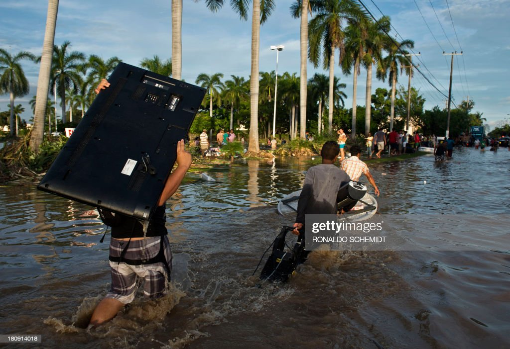 Looters carry goods from a supermarket in Acapulco, state of Guerrero, Mexico, on September 17, 2013 as heavy rains hit the country. Mexican authorities scrambled Tuesday to launch an air lift to evacuate tens of thousands of tourists stranded amid floods in the resort of Acapulco following a pair of deadly storms. The official death toll rose to 47 after the tropical storms, Ingrid and Manuel, swarmed large swaths of the country during a three-day holiday weekend, sparking landslides and causing rivers to overflow in several states.