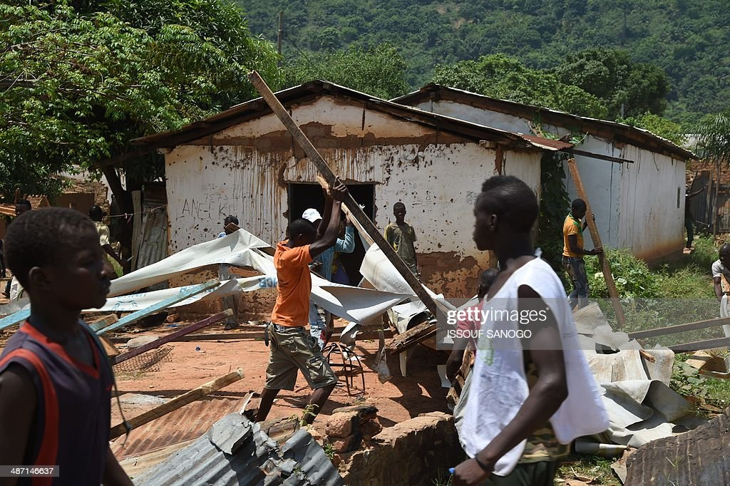 Looters carry pieces of wood from a mosque in the PK12 district, as soldiers of Sangaris and MISCA forces look on, on April 27, 2014 in Bangui, after about 1.300 Muslims who were hiding in this outskirts of the city left in a convoy escorted by the Misca African force, to be relocated in the north of the country.
