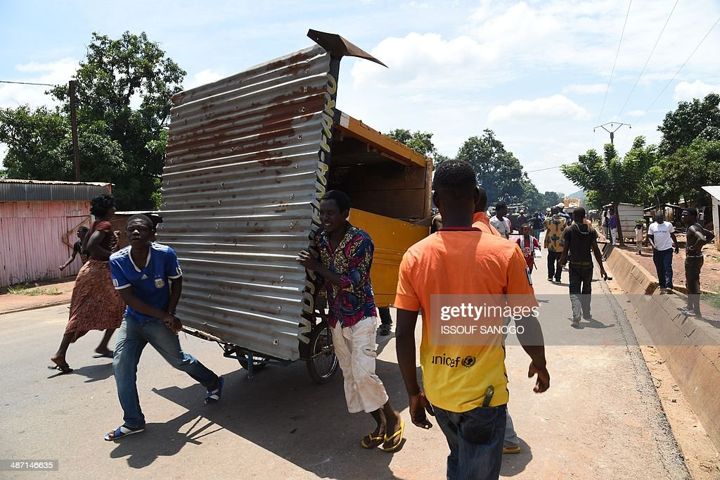Looters carry pieces of wood from the PK12 district, as soldiers of Sangaris and MISCA forces look on, on April 27, 2014 in Bangui, after about 1.300 Muslims who were hiding in this outskirts of the city left in a convoy escorted by the Misca African force, to be relocated in the north of the country.