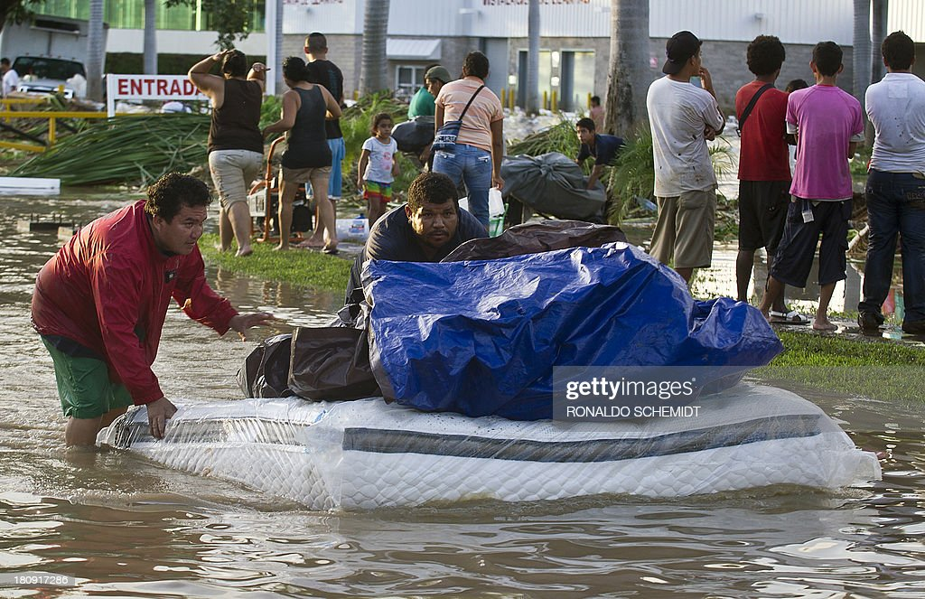 Looters flee with goods from a supermarket in Acapulco, state of Guerrero, Mexico, on September 17, 2013 as heavy rains hit the country. Mexican authorities scrambled Tuesday to launch an air lift to evacuate tens of thousands of tourists stranded amid floods in the resort of Acapulco following a pair of deadly storms. The official death toll rose to 47 after the tropical storms, Ingrid and Manuel, swarmed large swaths of the country during a three-day holiday weekend, sparking landslides and causing rivers to overflow in several states. AFP PHOTO/RONALDO SCHEMIDT