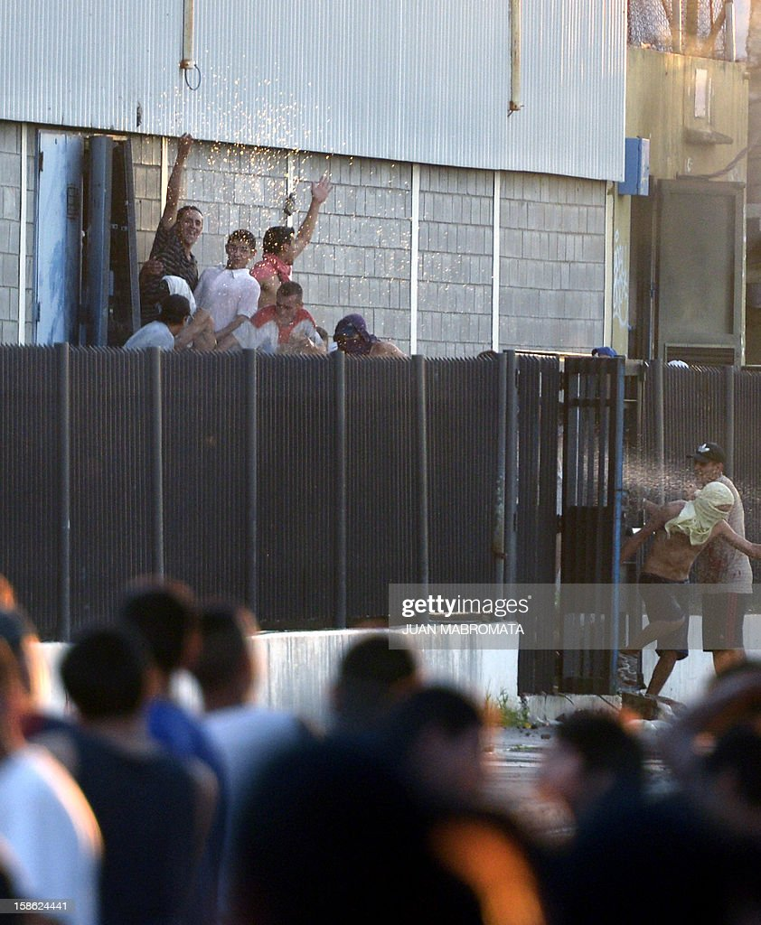 Looters force a lateral door of a supermarket in San Fernando, Buenos Aires province on December 21, 2012. Two people died Friday and two more were seriously injured as mobs looted supermarkets in Rosario, Argentina's third largest city, an official said. A series of lootings have taken place in five other cities of Argentina since Thursday leaving also near a hundred people injured and 300 detained. AFP PHOTO / JUAN MABROMATA