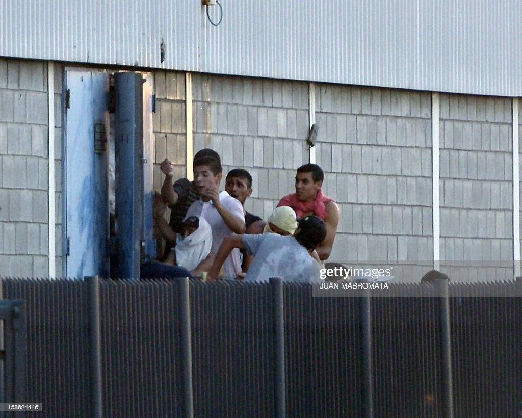 Looters force a lateral door of a supermarket in San Fernando, Buenos Aires province on December 21, 2012