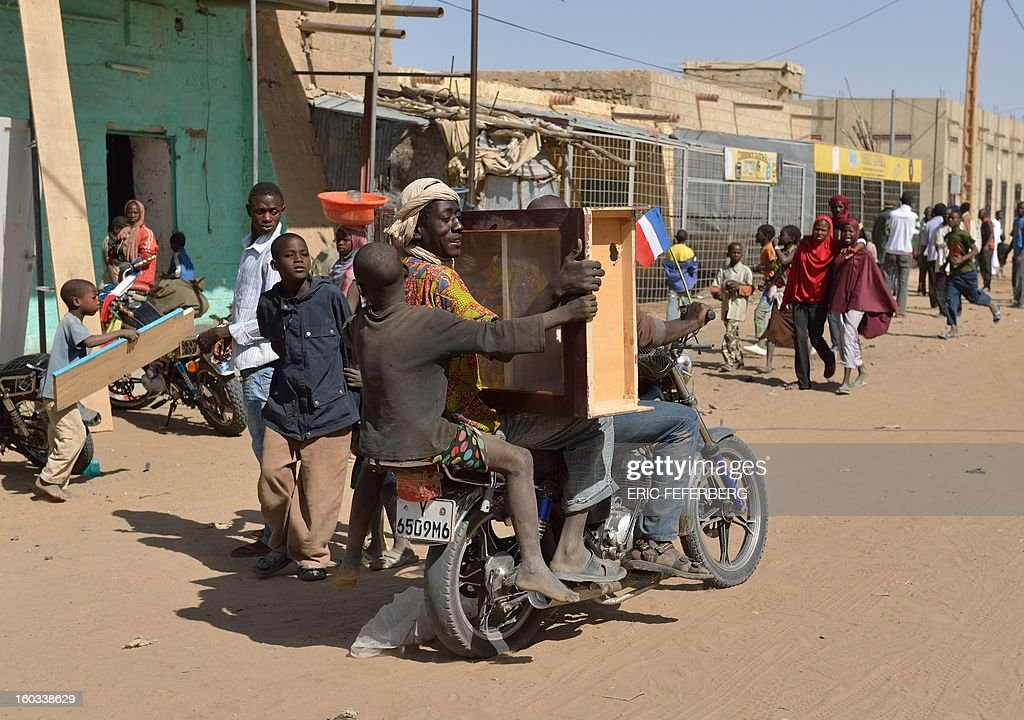 Looters leave with a cabinet on a motocycle on January 29, 2013 in Timbuktu after French-led troops freed the northern desert city on January 28 from Islamist control. Hundreds of Malians looted Arab-owned shops on January 29 in Timbuktu as global donors pledged over 455 million US dollars (340 million euro) at a donor conference in the Ethiopian capital Addis Ababa for military operations in Mali and humanitarian aid to rout the radicals from the north. AFP PHOTO / ERIC FEFERBERG