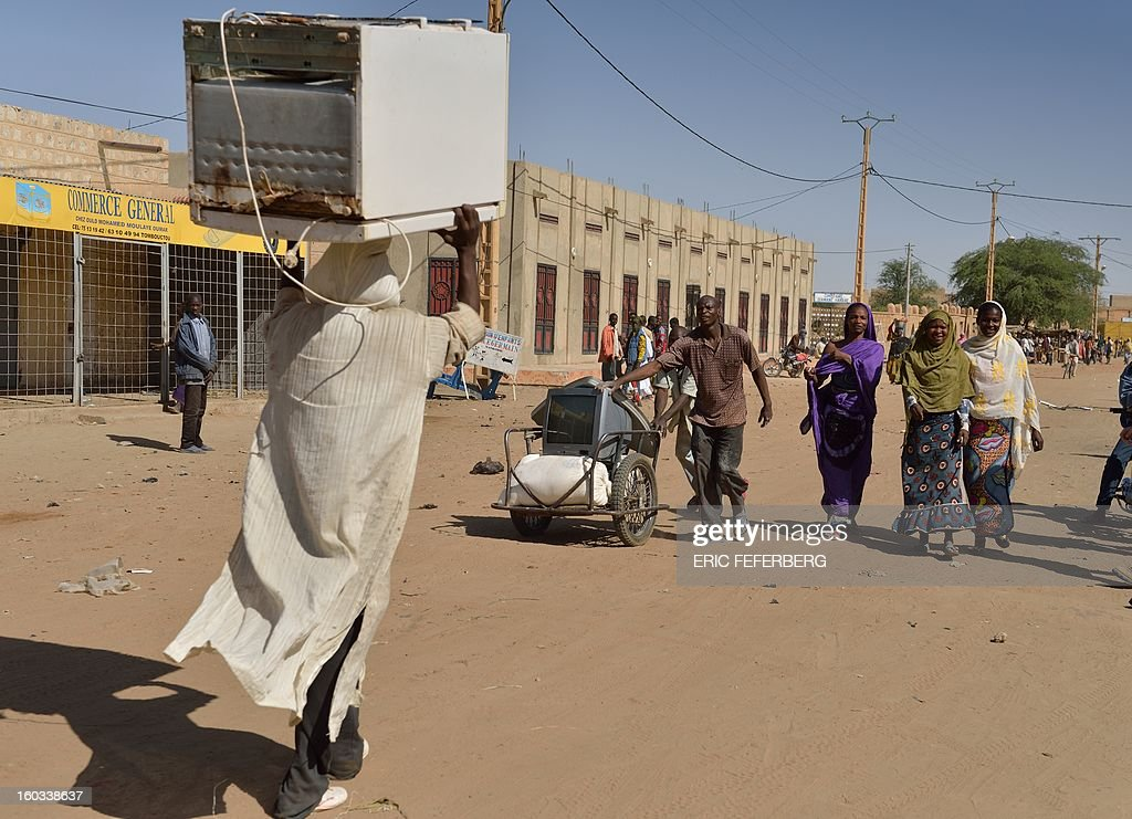 Looters leave with a TV and a fridge on January 29, 2013 in Timbuktu after French-led troops freed the northern desert city on January 28 from Islamist control. Hundreds of Malians looted Arab-owned shops on January 29 in Timbuktu as global donors pledged over 455 million US dollars (340 million euro) at a donor conference in the Ethiopian capital Addis Ababa for military operations in Mali and humanitarian aid to rout the radicals from the north.