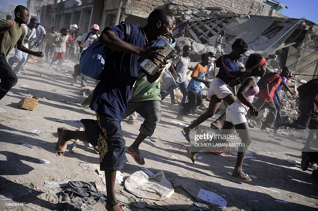 Looters run during a police assault January 17 2010 near the Hypolite Market in PortauPrince Aid is pouring into the earthquakestricken Caribbean...