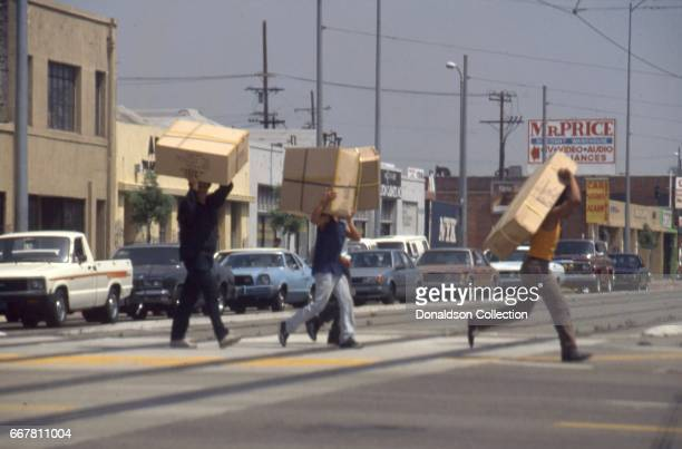 Looters take TV's across the street in widespread riots that erupted after the acquittal of 4 LAPD officers in the videotaped arrest and beating of...