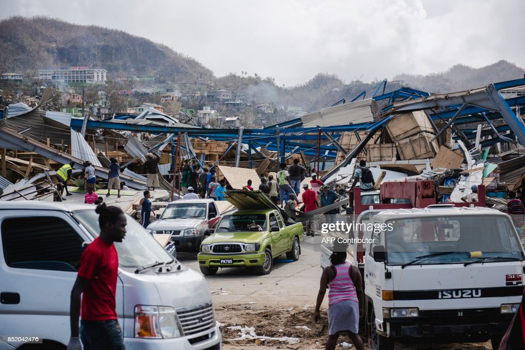 Looting is seen amid destruction September 22, 2017 in Canefield in the Caribbean island of Dominica, four days after the passage of Hurricane Maria. Maria previously tore through several Caribbean islands, claiming the highest toll on Dominica, which has a population of around 72,000 and has been largely cut off from the outside world. / AFP PHOTO / Lionel CHAMOISEAU